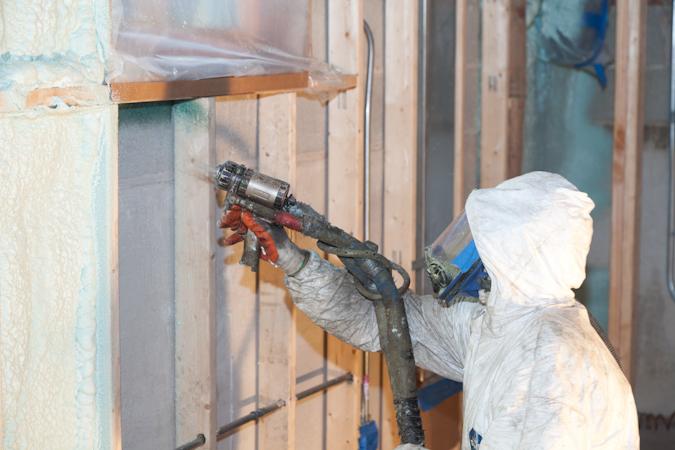 Spraying spray foam insulation