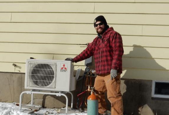 Man standing next to a heat pump