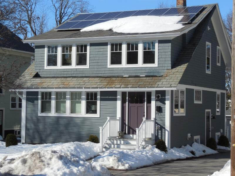 Two story house with snow covered solar panels on the roof